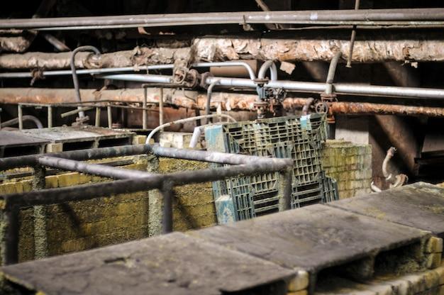 Промышленный интерьер старого здания завода, старая ржавая ванна с кислотой.