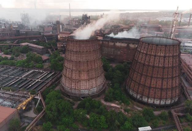 Индустриальный пейзаж на закате с высоты птичьего полета дым выходит из заводских труб