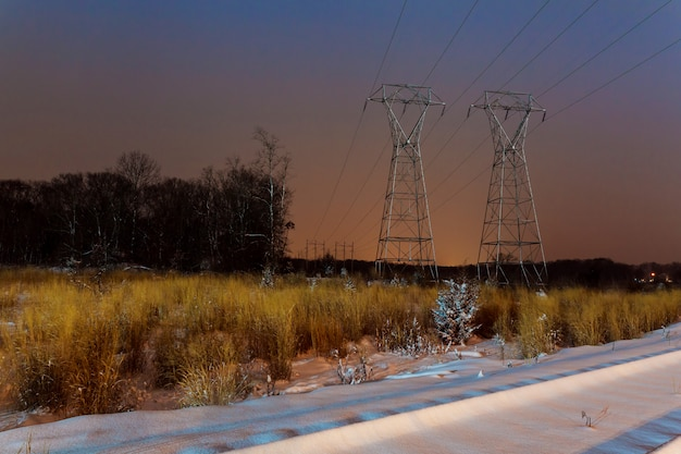 Industrial landscape - illuminated railway station by winter night with snowfall