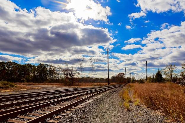 Индустриальный пейзаж - старая заброшенная промышленная зона в осеннем лесу, осеннее небо, облака, линия электропередачи, железная дорога