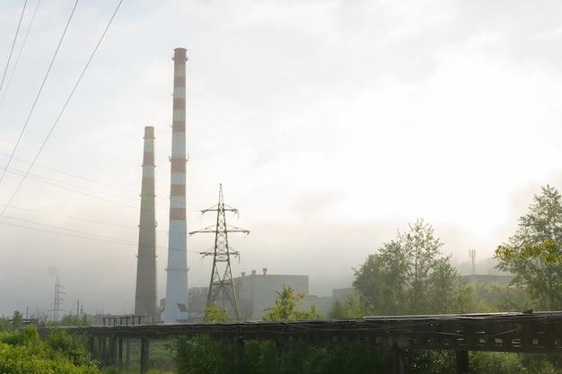 Индустриальный пейзаж - трубопроводы и дымоходы в утреннем тумане