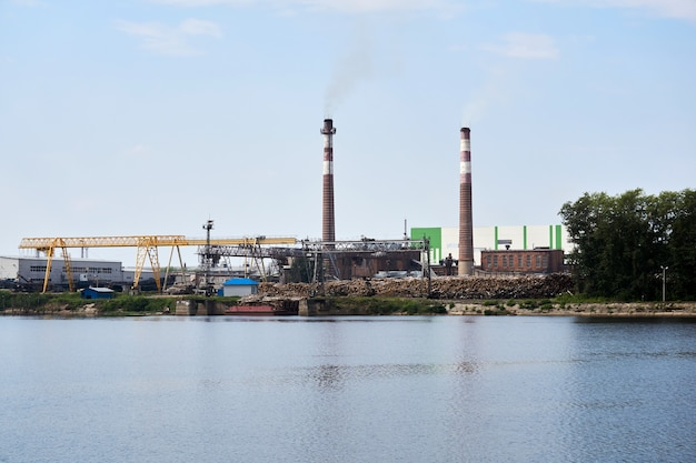 Industrial landscape, pulp and paper mill with stacks of logs and chimneys by the river