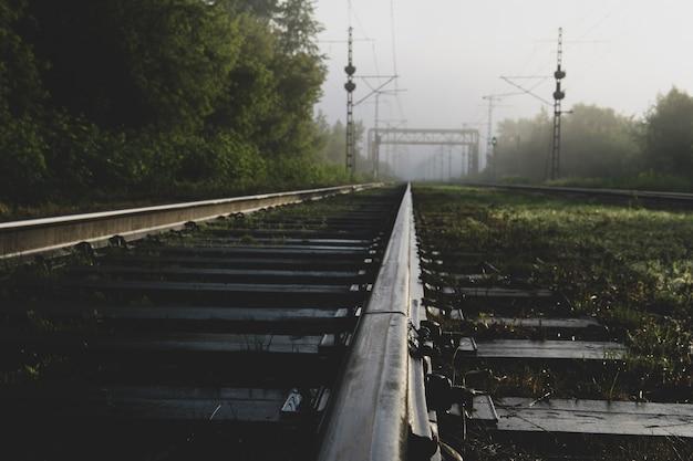 Индустриальный пейзаж - железнодорожные пути уходящие в утренний туман, вид снизу с рельсов