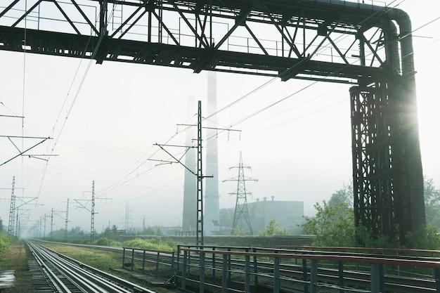 Индустриальный пейзаж, железнодорожные пути, уходящие в утренний туман, трубопроводы и дымоходы в тумане