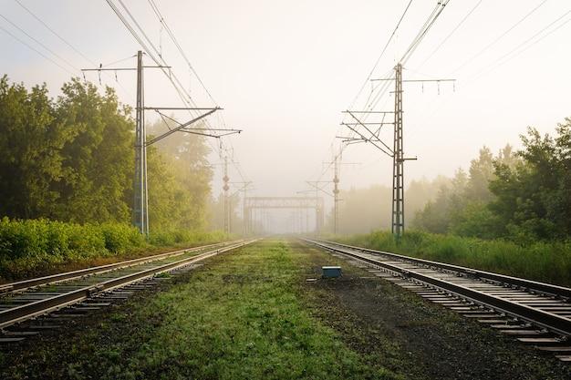 Индустриальный пейзаж - железнодорожные пути уходят в утренний туман