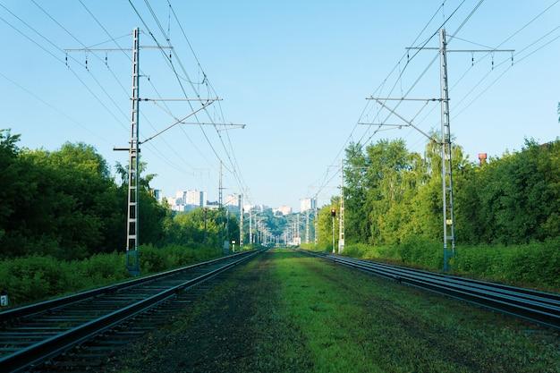 Индустриальный пейзаж - вдали железнодорожные пути, ведущие в город на холме.