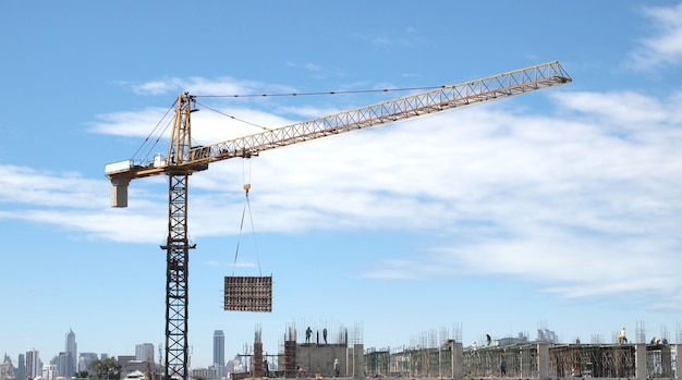 Industrial landscape with cranes on the blue sky