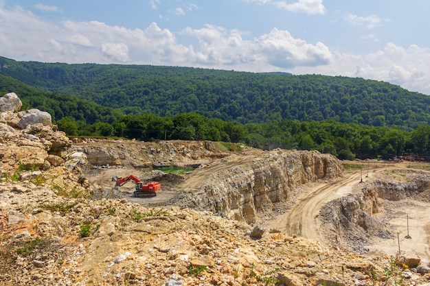 Industrial landscape with an excavator in a quarry for the extraction of limestone, gypsum and marble on a summer day