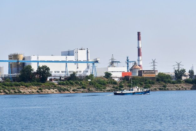 Industrial landscape with a factory on the banks of the river, along which a motorship floats