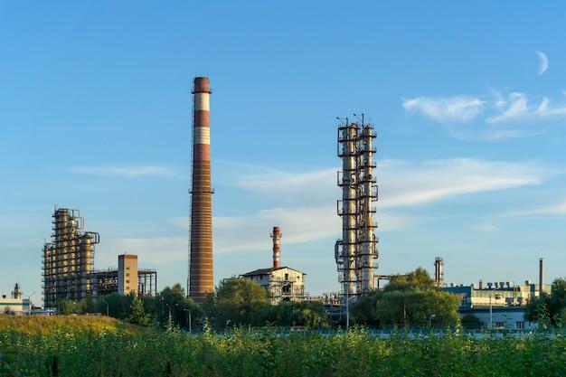 化学工場の充填蒸留塔と加熱炉のある産業景観。