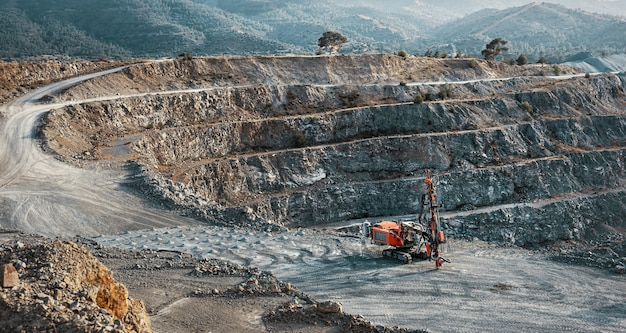 Industrial landscape with red stone crusher machine in gravel quarry