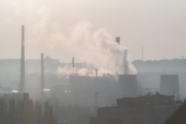 파이프에서 연기가 나는 산업 풍경, 주거용 건물 근처의 도시 공장