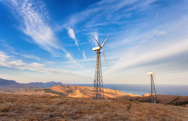 夕暮れ時の山で電気を生成する風力タービンの産業景観