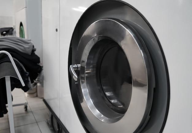 Industrial laundry washing machine in dry cleaner's workshop, closeup