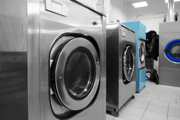 Industrial laundry washing machines in dry cleaner's workshop
