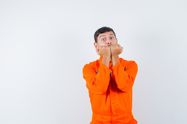 Промышленный мужчина эмоционально кусает кулаки в униформе и выглядит испуганным. передний план.