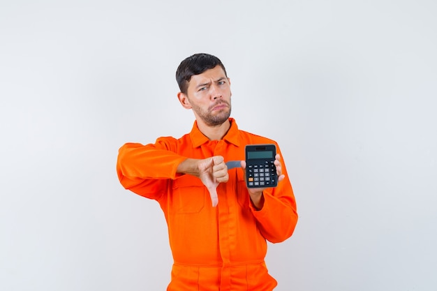 Industrial man holding calculator, showing thumb down in uniform and looking displeased , front view.