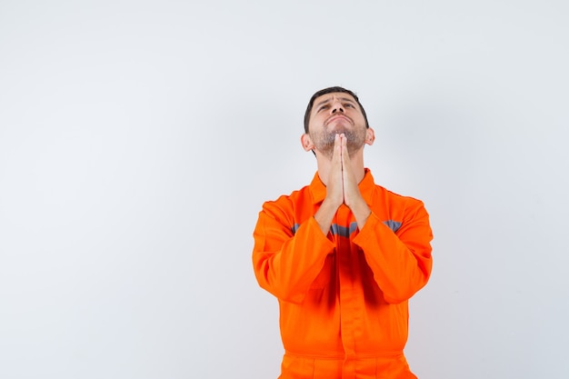 Industrial man holding hands in praying gesture in uniform and looking hopeful. front view.