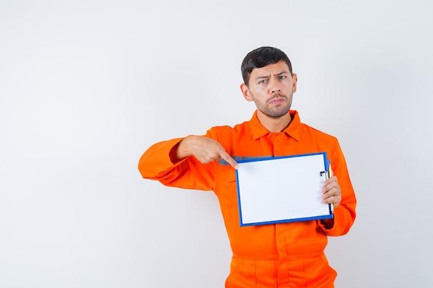 산업 남자 유니폼에 클립 보드를 가리키고 심각한, 전면보기를 찾고.