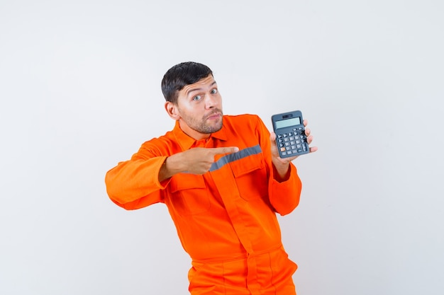 Industrial man pointing at calculator in uniform and looking optimistic. front view.