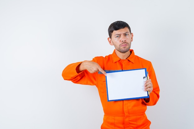 Industrial man pointing at clipboard in uniform and looking serious , front view.