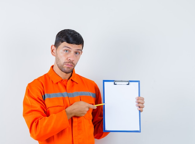 Industrial man pointing pencil at clipboard in uniform , front view.