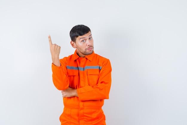Uomo industriale che indica in su in uniforme e che sembra esitante. vista frontale.