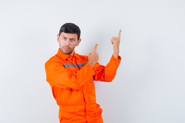 Industrial man pointing up in uniform and looking serious , front view.