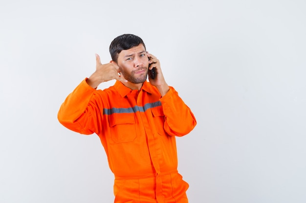 Industrial man talking on mobile phone with phone gesture in uniform front view.