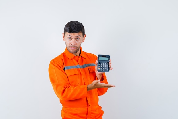 Industrial man in uniform showing calculator and looking confident , front view.