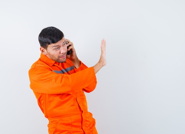 Industrial man in uniform talking on mobile phone with stop gesture , front view.