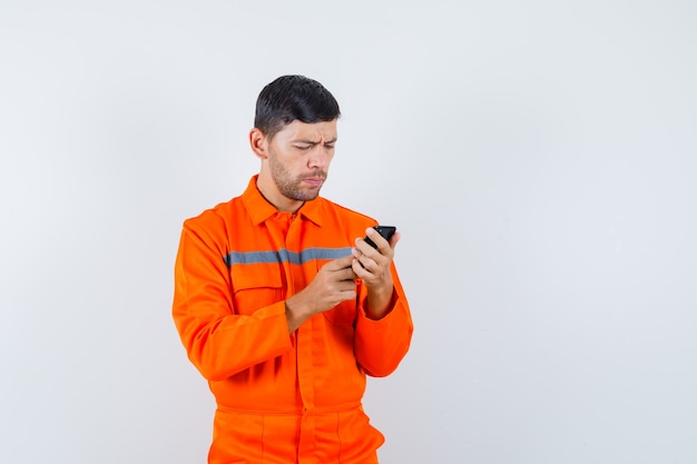 Industrial man using mobile phone in uniform and looking busy , front view.