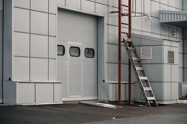 산업용 금속 창고 문. 롤러 셔터 도어. 빨간 철과 나무 계단입니다. 전형적인 근무일.