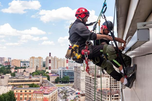 産業登山労働者が設置中に住宅の建物にぶら下がっている