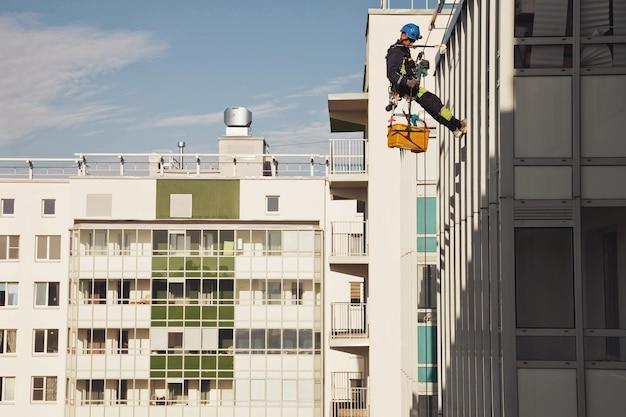 산업 등산 작업자가 외부 외관 유리를 세척하는 동안 주거용 건물에 매달려 있습니다. 로프 접근 작업자가 집 벽에 걸려 있습니다. 도시 작품의 개념입니다. 복사 공간