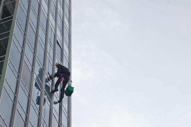 産業登山労働者は、外壁の窓ガラスを洗っている間、住宅の建物にぶら下がっています。ロープアクセス労働者が家の壁にぶら下がっています。都市作品のコンセプト。コピースペース