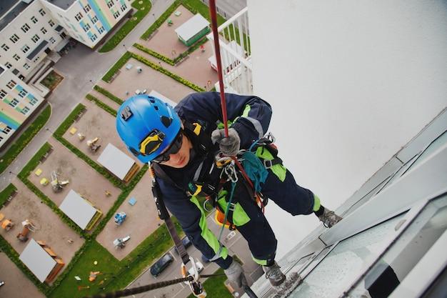 産業登山労働者は、外壁の窓ガラスを洗っている間、住宅の正面の建物にぶら下がっています。ロープアクセス労働者が家の壁にぶら下がっています。都市作品のコンセプト。サイトのコピースペース