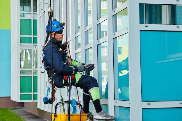 工業用登山労働者は、外壁のガラスを洗浄しながら、住宅の正面の建物にぶら下がっています。ロープアクセス労働者が家の壁にぶら下がっています。都市作品のコンセプト。サイトのコピースペース