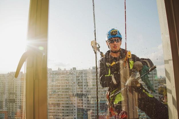 산업 등산 작업자는 외부 외관 유리를 세척하는 동안 주거용 외관 건물에 매달려 있습니다. 로프 접근 작업자가 집 벽에 걸려 있습니다. 도시 작품의 개념입니다. 사이트 복사 공간