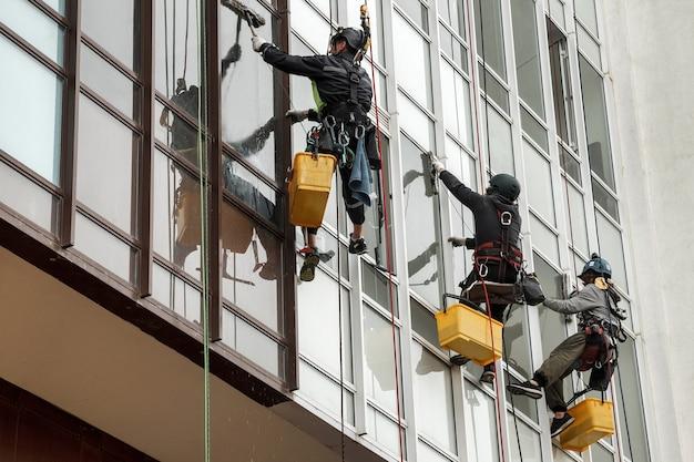 産業登山労働者は、外壁の窓ガラスを洗っている間、住宅の正面の建物にぶら下がっています。ロープアクセス労働者は家の壁にぶら下がっています。産業都市作品のコンセプト。コピースペース