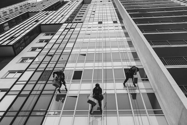 산업 등산 노동자는 외부 외관 유리를 세척하는 동안 주거용 외관 건물에 매달려 있습니다. 로프 접근 인부들이 집 벽에 걸려 있습니다. 산업 도시 작품의 개념입니다. 복사 공간