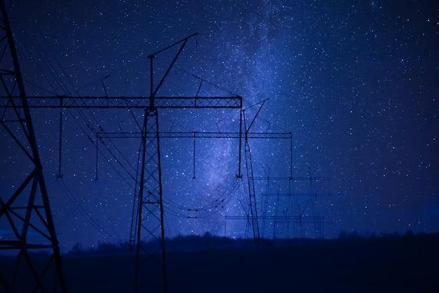 고전압 전력선, 전기 타워 및 별이있는 산업 밤 풍경