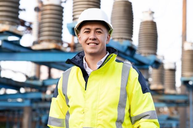 ヘルメットをかぶって立っているアジアのエコロジー労働者の産業の人々の持続可能なエネルギーの肖像画