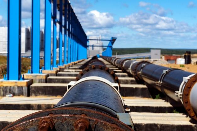 Промышленный трубопровод, выходящий в перспективу на наземные сооружения современного рудника