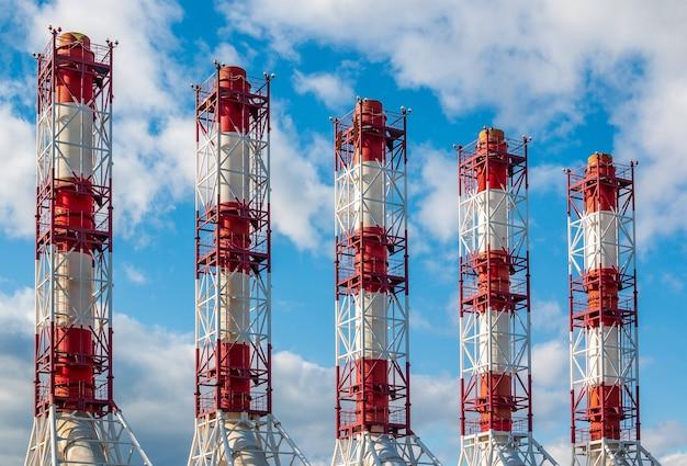 Промышленные трубы электростанции на фоне голубого неба