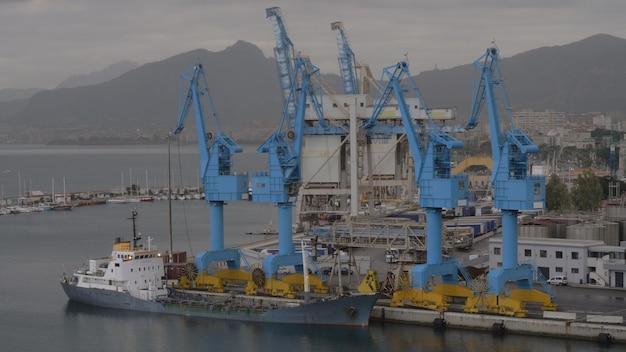 컨테이너 크레인과 정박된 화물선이 있는 산업 항구, 먼 해안 도시와 산을 배경으로