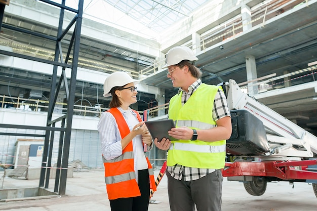 Industrial portrait of male and female engineers in construction of commercial administrative building