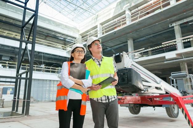 Индустриальный портрет инженеров мужского и женского пола при строительстве коммерческого административного здания