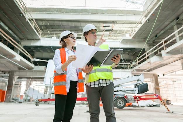 상업 행정 건물 건설에서 남녀 엔지니어의 산업 초상화