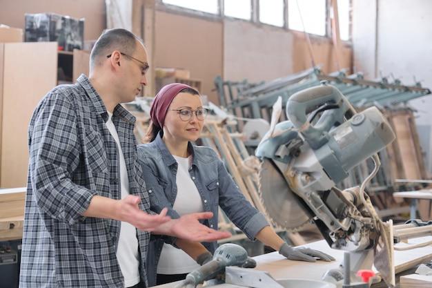 Промышленный портрет двух работающих мужчин и женщин, разговаривающих на станках